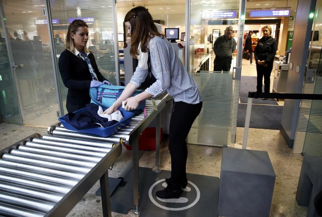 A staff demonstrates a special carpet, developed by Swiss company Sedect, that detect metallic parts in passengers shoes and accessories before they pass the security gates, at Cointrin airport in Geneva, Switzerland, November 24, 2016. (Photo by Denis Balibouse/Reuters)