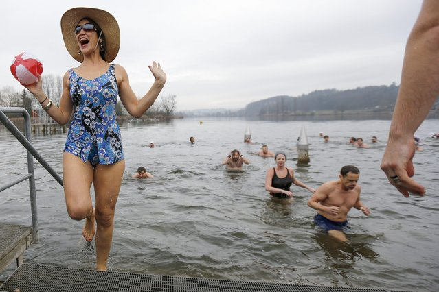 Brave swimmers get out of the four degree Celsius cold water of the Moossee lake at Moosseedorf, Switzerland, 31 December 2015, after their traditional New Year's Eve swim. (Photo by Peter Klaunzer/EPA)