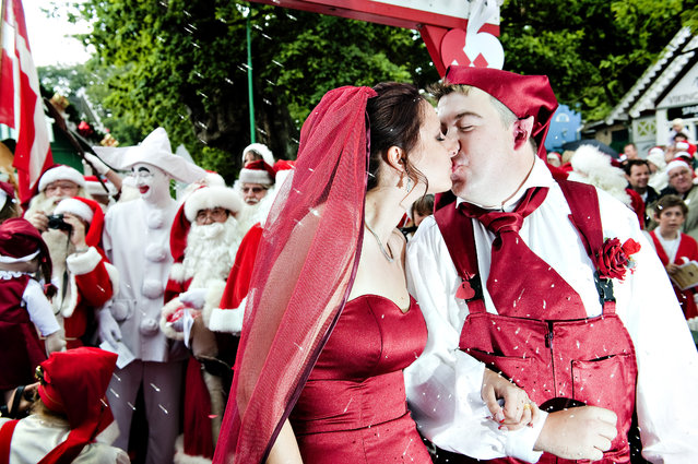 Newlyweds Sine Andersen and Rune Jamrath (R) who is dressed as a pixie, kiss during their wedding at the World Santa Claus Congress 2009, at the amusement park Bakken north of Copenhagen July 20, 2009.  More than 150 Santas from all over the world convened for the 52nd congress. The father of the bride (background 2nd L) is the Bakken amusement park Pirrot. (Photo by Casper Christoffersen/Reuters/Scanpix)