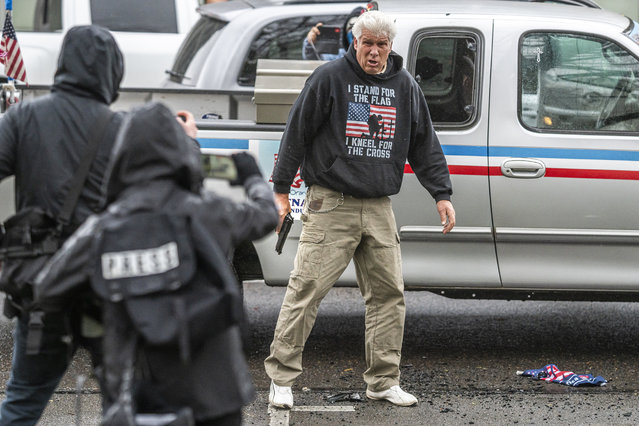 A driver pulls a handgun on protesters after they broke his trucks lights on March 28, 2021 in Salem, Oregon. The protesters clashed with occupants of vehicles that had participated in an American flag-waving car caravan, despite law enforcements efforts to to keep the groups separate. (Photo by Nathan Howard/Getty Images)