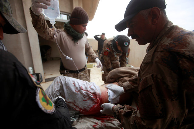 Iraqi security forces provide medical assistance for an injured man, during a battle with Islamic State militants in Mosul, Iraq, November 30, 2016. (Photo by Alaa Al-Marjani/Reuters)