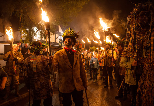 Members of the Leominster Morris lead the crowd from the Boot Inn in Orleton near Leominster to the local apple orchard to take part in a their Twelfth Night wassailing ceremony on January 6, 2016 in Herefordshire, England. The annual tradition sees morris dancers and mummers gathering at the pub before processing to a local orchard to perform a ceremony that involves placing a cider-soaked piece of Christmas cake on the branches of an apple tree and sprinkling cider around its roots, before lighting torches, dancing and singing the Wassail Song as to ensure a good crop of cider apples for the year ahead. (Photo by Matt Cardy/Getty Images)