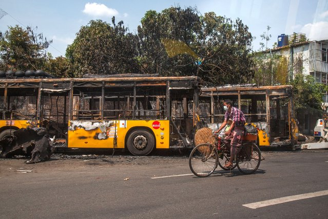 A man bikes past burnt public transport buses parked at Kyimyindaing township in Yangon, Myanmar Monday, April 12, 2021. Local news media reported that the buses got burned early Monday morning, but provided no details for the cause. (Photo by AP Photo/Stringer)