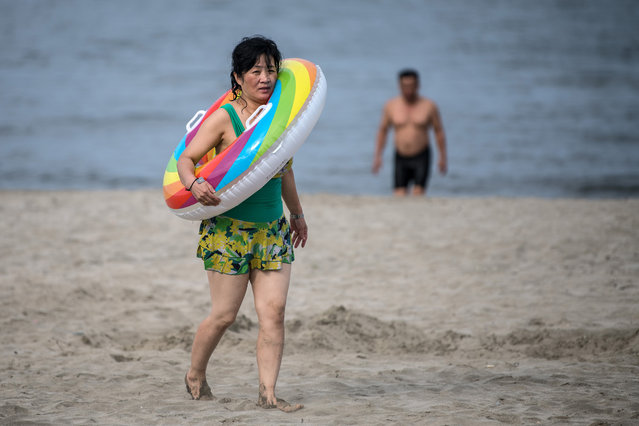 A woman carries an inflatable ring as she walks on a beach on August 22, 2018 in Wonsan, North Korea. (Photo by Carl Court/Getty Images)