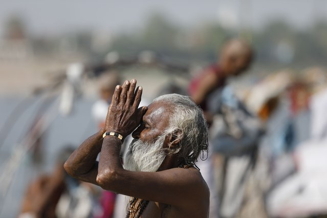 A Hindu man offers prayers at the confluence of rivers Ganges and Yamuna in Prayagraj, India, Sunday, April 25, 2021. After having largely tamed the virus last year, India is in the throes of the world's worst coronavirus surge and many of the country's hospitals are struggling to cope with shortages of beds, medicines and oxygen. (Photo by Rajesh Kumar Singh/AP Photo)