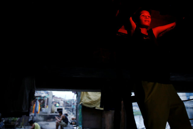 A man enters a space in which he lives under C-3 bridge in North Bay Boulevard South (NBBS), a Navotas City district of slums and waterways with a high number of drug war deaths, in Manila, Philippines November 3, 2016. (Photo by Damir Sagolj/Reuters)