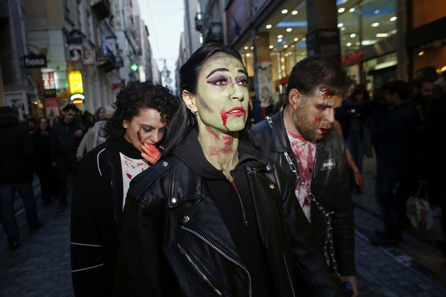 Revellers dressed as zombies walk through the city centre during an annual zombie walk in Athens, February 21, 2015. (Photo by Kostas Tsironis/Reuters)