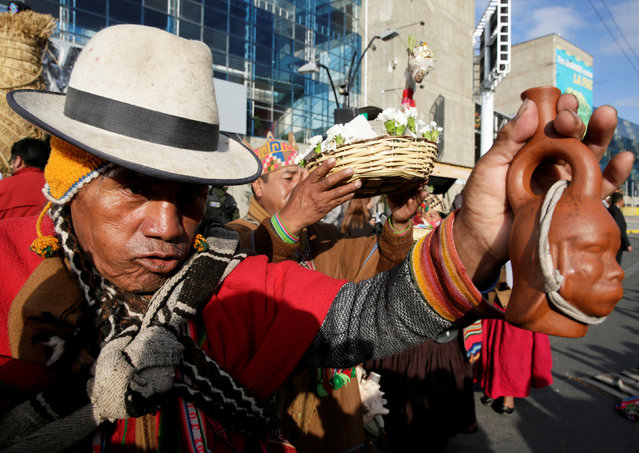 """Aymara witch doctors perform during a farewell ceremony  of the totora reeds """"Viracocha III"""", a boat made only from the reed, as it is being prepared to cross the Pacific from Chile to Australia on an expected six-month journey, in La Paz, Bolivia December 15, 2016. (Photo by David Mercado/Reuters)"""