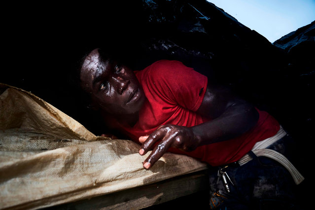 A Malian sand digger takes shelter under a plastic tarpaulin during a storm over the Niger River, near Kangaba in Mali' s southwestern Koulikoro region, on October 1, 2018. (Photo by Michele Cattani/AFP Photo)