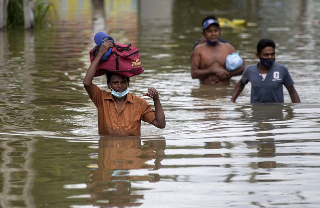 Sri Lankans wade through an inundated street following heavy rainfall at Malwana, on the outskirts of Colombo, Sri Lanka, Saturday, June 5, 2021. Flash floods and mudslides triggered by heavy rains in Sri Lanka have killed at least four people and left seven missing, while more than 5,000 are displaced, officials said Saturday. Rains have been pounding six districts of the Indian Ocean island nation since Thursday night, and many houses, paddy fields and roads have been inundated, blocking traffic. (Photo by Eranga Jayawardena/AP Photo)