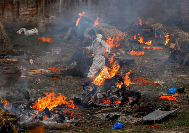 A man wearing personal protective equipment (PPE) runs past the burning pyres during a mass cremation of people, who died from the coronavirus, at the crematorium, in Kathmandu, Nepal on May 11, 2021. (Photo by Navesh Chitrakar/Reuters)