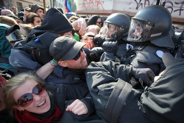 Protesters and police clash during a demonstration on the occasion of the opening of the new headquarters of the European Central Bank (ECB) in Frankfurt, Germany, 18 March 2015. German authorities arrested about 300 people in Frankfurt amid violent anti-austerity protests at the opening of a new headquarters for the European Central Bank (ECB), police said. (Photo by Frederik von Erichsen/EPA)