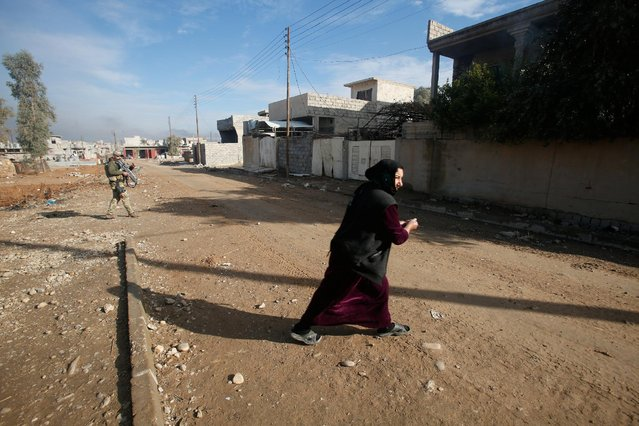 A woman walks across the street during a fight with Islamic State militants in Intisar district of eastern Mosul, Iraq, December 22, 2016. (Photo by Khalid al Mousily/Reuters)