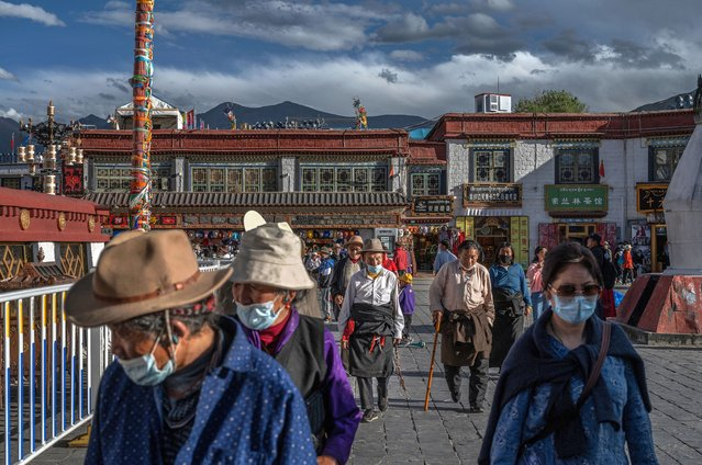 Tibetan Buddhists walk the kora in front the Jokhang Temple, a UNESCO heritage site, on June 1, 2021 in Lhasa, Tibet Autonomous Region, China. (Photo by Kevin Frayer/Getty Images)