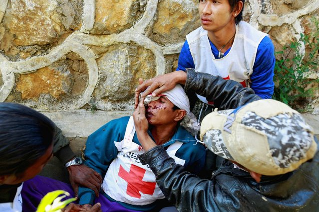A volunteer with the Myanmar Red Cross Society, is helped after being wounded when the convoy he was in, was fired upon by the Myanmar National Democratic Alliance Army (MNDAA), according to the Myanmar army, between the capital of Kokang, Laukkai, and Chinshwehaw, February 17, 2015. (Photo by Soe Zeya Tun/Reuters)