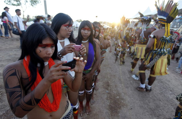 Brazilian indigenous people take a photograph before attending the opening ceremony of the XII Games of the Indigenous People in Cuiaba November 9, 2013. (Photo by Paulo Whitaker/Reuters)