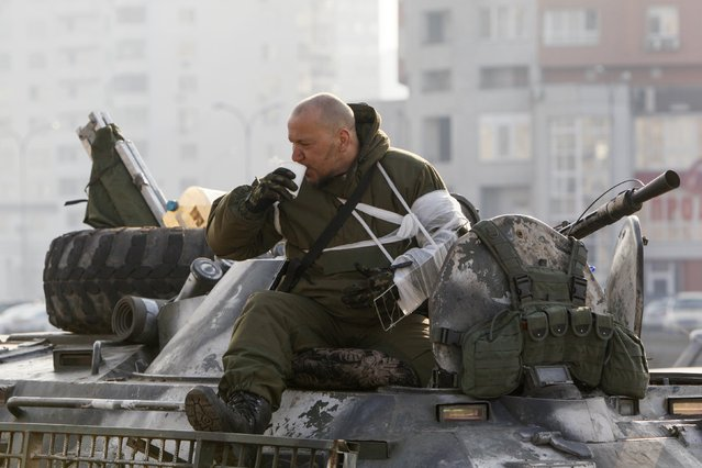 A Ukrainian serviceman drinks coffee atop an armoured personnel carrier (APC) in Kiev, as he returns from the frontline in eastern Ukraine, March 11, 2015. (Photo by Valentyn Ogirenko/Reuters)