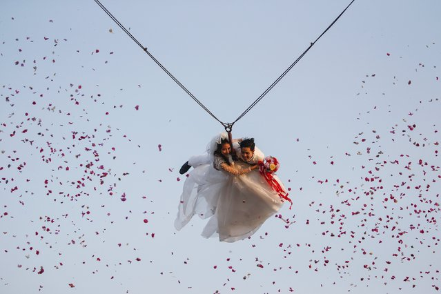Bride Jintara Promchat, 28, and groom Kittinant Suwansiri, 29, fly while attached to cables during a wedding ceremony ahead of Valentine's Day at a resort in Ratchaburi province, Thailand, February 13, 2016. (Photo by Athit Perawongmetha/Reuters)
