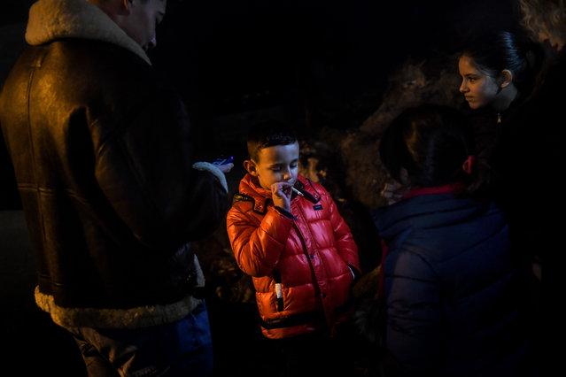 A child stands with other villagers as he smokes a cigarette during Epiphany celebrations in Vale de Salgueiro, northern Portugal, on January 5, 2019. In the village of Vale de Salgueiro, in northern Portugal, children as young as five are allowed to smoke cigarettes according to the local tradition of the Christian Epiphany celebrations. (Photo by Patrícia de Melo Moreira/AFP Photo)