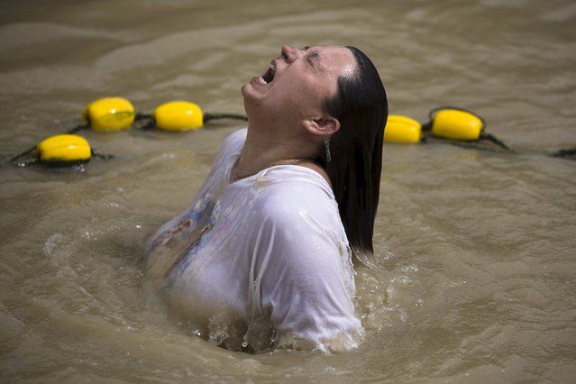 A Christian pilgrim dips in the water during her visit to the baptismal site known as Qasr el-Yahud on the banks of the Jordan River, near the West Bank city of Jericho, April 9, 2015. (Photo by Amir Cohen/Reuters)