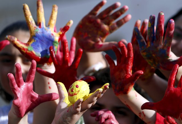 Children pose with painted hands and an Easter egg ahead of Easter celebrations in Abra April 4, 2015. (Photo by Ali Hashisho/Reuters)