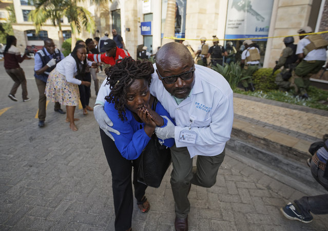 Civilians flee the scene at a hotel complex in Nairobi, Kenya Tuesday, January 15, 2019. Terrorists attacked an upscale hotel complex in Kenya's capital Tuesday, sending people fleeing in panic as explosions and heavy gunfire reverberated through the neighborhood. (Photo by Ben Curtis/AP Photo)