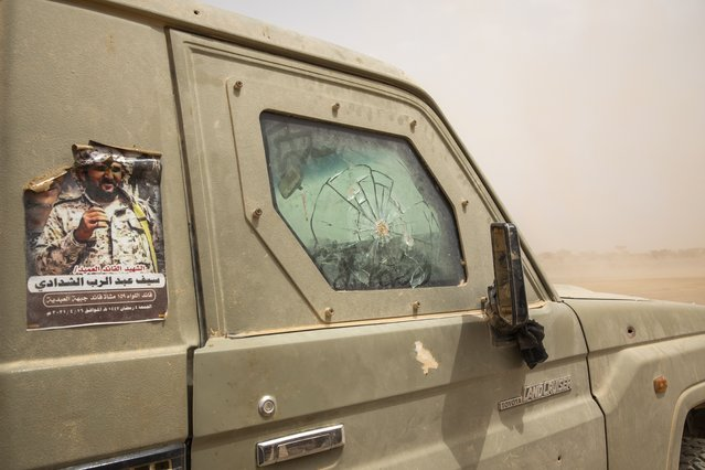 """Yemeni fighters drive their damaged armored vehicle with a poster of a commander brigadier general and Arabic that reads, """"martyr commander brigadier general Self Abd al-Rab al-Shadady"""", who was killed in clashes with Houthi rebels, on the Mass front line, in Marib, Yemen, Saturday, June 19, 2021. On the most active front line in Yemen's long civil war, the months-long battle for the city of Marib has become a dragged-out grind with a steady stream of dead and wounded from both sides. (Photo by Nariman El-Mofty/AP Photo)"""