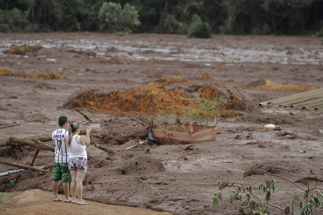 A couple with missing relatives look at the flooded area, after a dam collapsed in Brumadinho, Brazil, Saturday, January 26, 2019. An estimated 300 people were still missing and authorities expected the death toll to rise during a search made more challenging by intermittent rains. (Photo by Andre Penner/AP Photo)