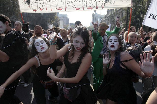 Youths participate in a protest march in Santiago, Chile, Thursday, April 16, 2015. (Photo by Luis Hidalgo/AP Photo)