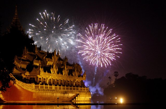 Fireworks from Myanmar's second time public New Year countdown rise as Karawake raft lies in Kandawgyee lake during earlier minutes of 2014, Yangon, Myanmar, 01 January 2014. (Photo by Lynn Bo Bo/EPA)