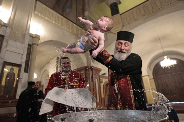 A baby is baptized during a mass baptism ceremony on Orthodox Epiphany Day in the Holy Trinity Cathedral in Tbilisi, Georgia, Thursday, January 19, 2017. Orthodox Georgians celebrate Epiphany on Jan. 19, following the old Julian calendar. (Photo by Shakh Aivazov/AP Photo)
