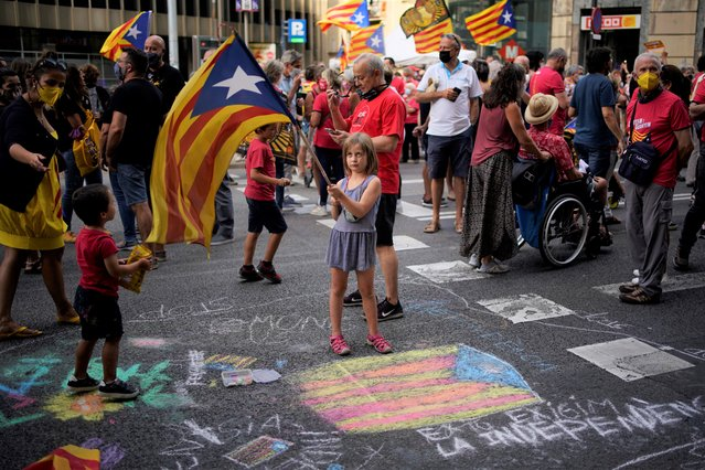 A girl waves a pro-independence flag as demonstrators march during the Catalan National Day in Barcelona, Spain, Saturday, September 11, 2021. Thousands of Catalans have rallied for independence from the rest of Spain in their first major mass gathering since the start of the pandemic. The march in Barcelona on Saturday comes before a meeting between regional leaders in northeast Catalonia and the Spanish government. (Photo by Joan Mateu Parra/AP Photo)