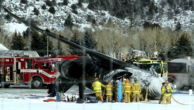 Emergency crews work near a passenger plane that crashed upon landing at the Aspen-Pitkin County Airport in Aspen, Colo., Sunday, January 5, 2014. (Photo by Leigh Vogel/AP Photo/The Aspen Times)