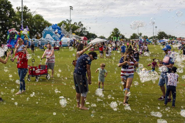 Children and parents play with bubbles at a Fourth of July celebration in McKinney, Texas on July 3, 2021. (Photo by Chris Rusanowsky/ZUMA Wire/Rex Features/Shutterstock)