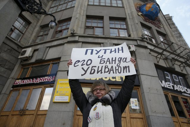"An opposition supporter holds a placard during a lone picket in central Moscow April 19, 2015. The sign reads, ""Putin and his gang kill"". (Photo by Maxim Zmeyev/Reuters)"