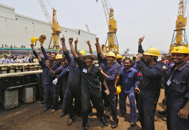 Employees cheer as the newly built Indian Naval warship INS Visakhapatnam sails into the Arabian Sea during its launch at Mazagon Docks, a naval vessel ship building yard, in Mumbai April 20, 2015. (Photo by Shailesh Andrade/Reuters)