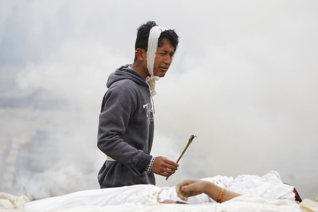 A Nepalese man performs rituals during the cremation of his mother who died in the earthquake in Bhaktapur near Kathmandu, Nepal, Sunday, April 26, 2015. (Photo by Niranjan Shrestha/AP Photo)