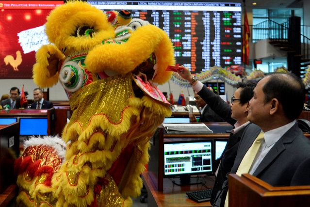 A trader gives a red envelope containing money to a lion dance performer at the trading floor of the Philippine Stock Exchange to celebrate the Chinese Lunar New Year of the Rooster in Makati city, Metro Manila, Philippines January 30, 2017. (Photo by Ezra Acayan/Reuters)