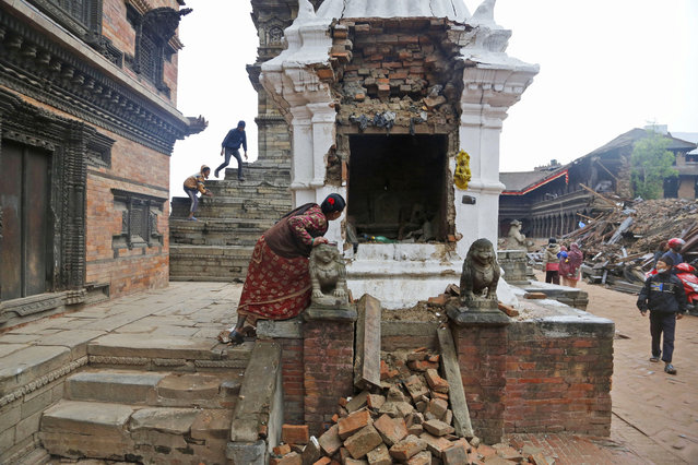 A Nepalese woman looks inside a damaged temple and prays in Bhaktapur near Kathmandu, Nepal, Thursday, April 30, 2015. (Photo by Manish Swarup/AP Photo)