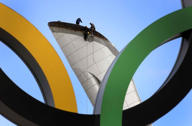 Workers check the Olympic cauldron at the Olympic Park's medals plaza in the seaside cluster prior to the start of the 2014 Sochi Winter Olympics on February 2, 2014 in Sochi. (Photo by Alexander Nemenov/AFP Photo)