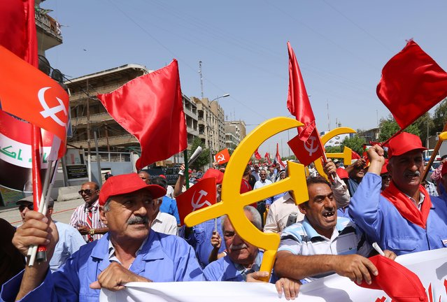 Supporters of the Iraqi Communist Party take part in a May Day celebration in Baghdad, Iraq, Friday, May 1, 2015. May 1 is celebrated as the International Labor Day or May Day across the world. (Photo by Hadi Mizban/AP Photo)