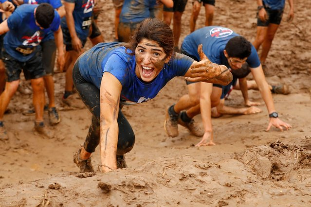 "Participants climb a 10km muddy obstacle course during the ""Run Mud"" race, on March 29, 2019 in the Israeli mediterranean coastal city of Tel Aviv. (Photo by Jack Guez/AFP Photo)"