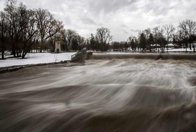 Cayuga Creek water rushes past a neighbourhood following a massive snow storm in Lancaster, New York November 24, 2014. Emergency workers filled thousands of sandbags on Sunday as the area around Buffalo, New York braced for potential flooding as warming temperatures began to melt up to seven feet (2 metres) of snow. (Photo by Mark Blinch/Reuters)