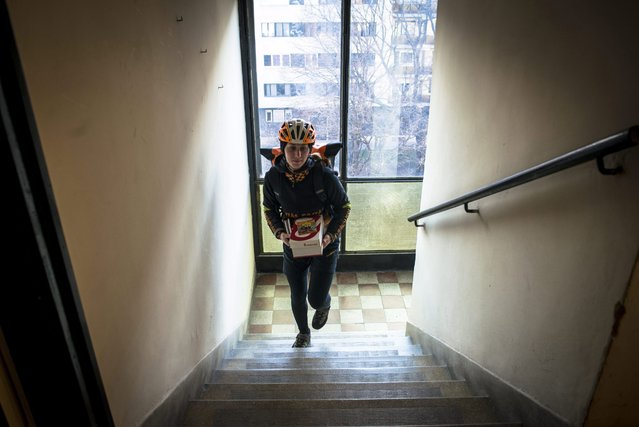 Bicycle courier Aliz Szaloky delivers a parcel in the staircase of a block of flats in southern Budapest, Hungary, 26 February 2016. (Photo by Bea Kallos/EPA)