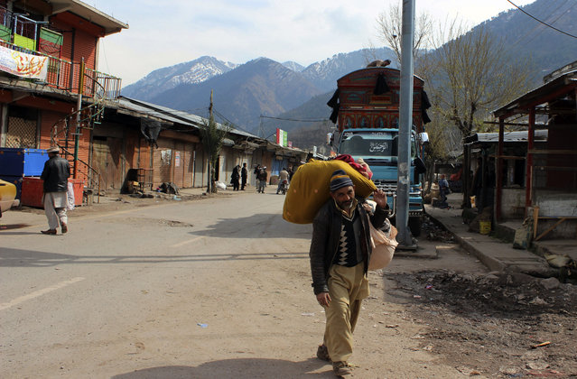 A Pakistani Kashmiri carries his belonging and walks through a market at his hometown in Chakoti on the violent border that separates the Himalayan region of Kashmir between Pakistan and India, Saturday, March 2, 2019. Indian and Pakistani soldiers again targeted each other's posts and villages along their volatile frontier in disputed Kashmir, killing at some civilians and wounding few others, officials said. (Photo by Roshan Mughal/AP Photo)