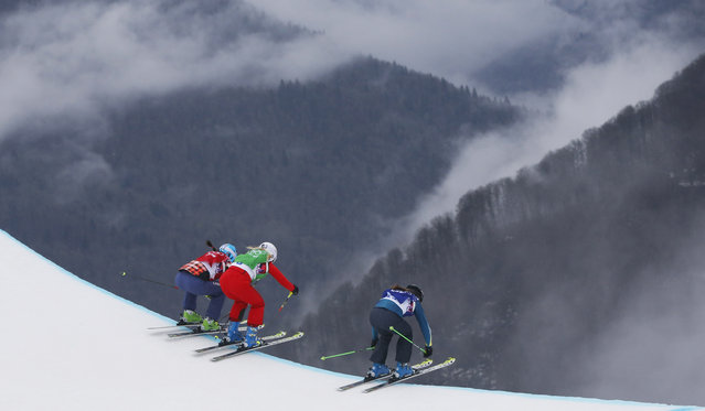 Comeptitors, from left, Canada's Marielle Thompson, Switzerland's Sanna Luedi, and Australia's Katya Crema take a jump during a women's ski cross quarterfinal at the Rosa Khutor Extreme Park, at the 2014 Winter Olympics, Friday, February 21, 2014, in Krasnaya Polyana, Russia. (Photo by Sergei Grits/AP Photo)