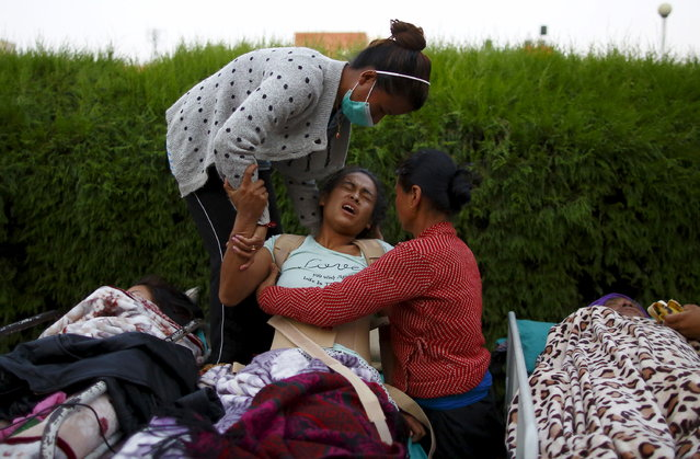 An earthquake victim reacts in pain after being moved out from the hospital to the open ground for treatment, in Kathmandu, May 12, 2015. (Photo by Navesh Chitrakar/Reuters)