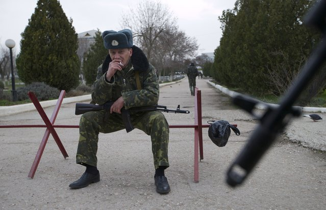 An armed Ukrainian airman smokes as he and others guard what's left under their control at the Belbek air base, outside Sevastopol, Ukraine, on Tuesday, March 4, 2014. (Photo by Ivan Sekretarev/AP Photo)