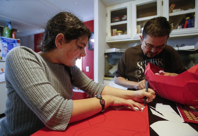In this photo taken April 15, 2015,, Clay Hielscher and his 11-year-old daughter, Kyrianna, work on a battlesuit in their Overbook, Kan., home. (Photo by Chris Neal/AP Photo/The Topeka Capital-Journal)