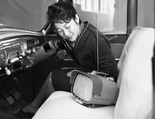 Tomiko Kawabata sits in her car and admires her new all-transistor, portable television set which Sony put into mass production, in Tokyo, on January 5, 1960. The set, which has an eight-inch screen, is powered by a storage battery good for three hours when used outdoors and it can be operated on an AC 200-volt current indoors. (Photo by AP Photo via The Atlantic)